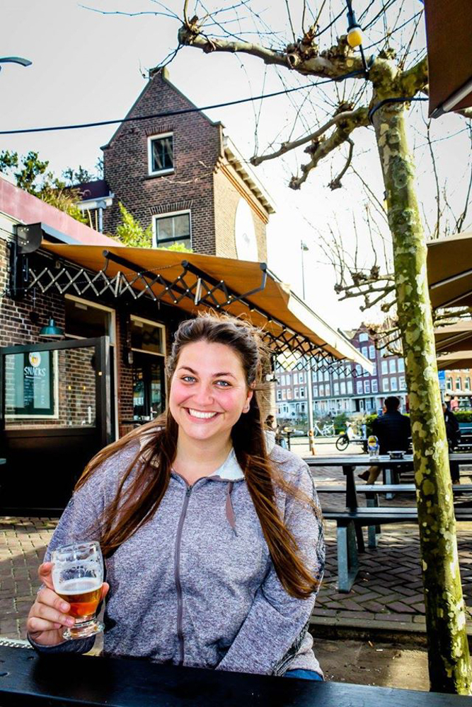 Girl drinking a beer in Amsterdam
