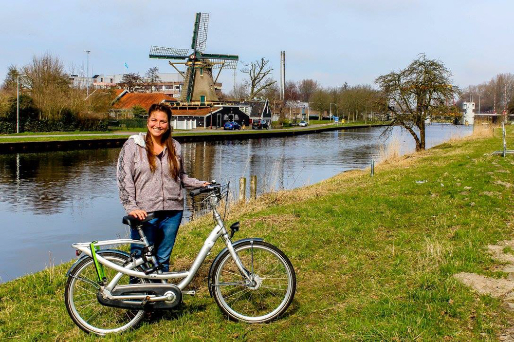 Girl with a bike in front of a windmill in Amsterdam
