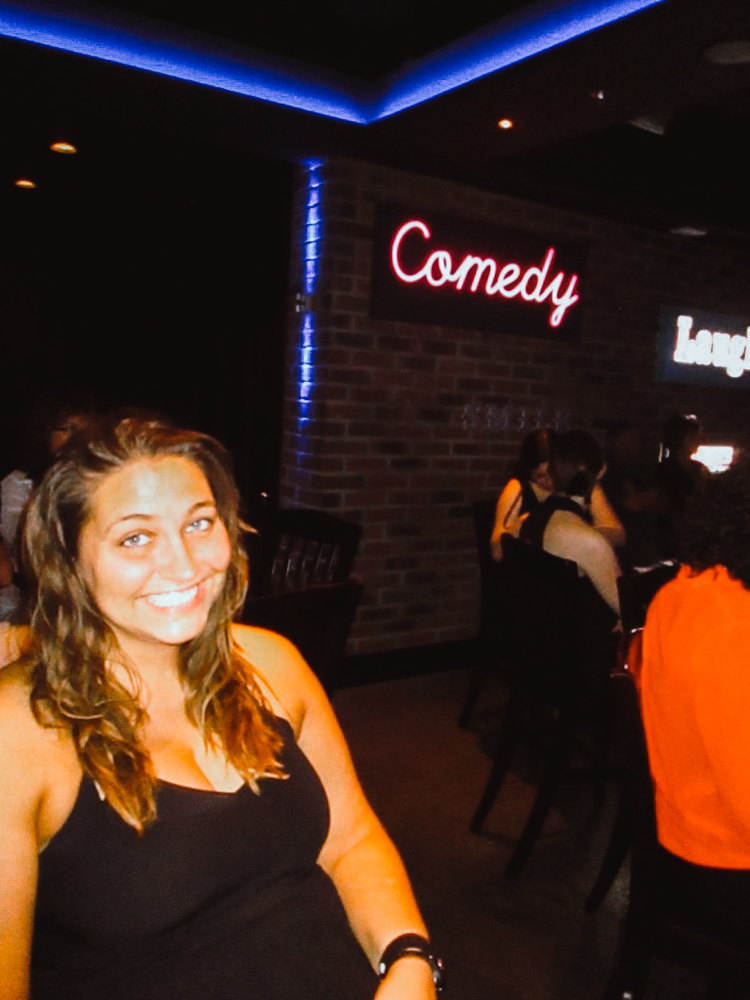 Girl sitting, smiling at a comedy show.