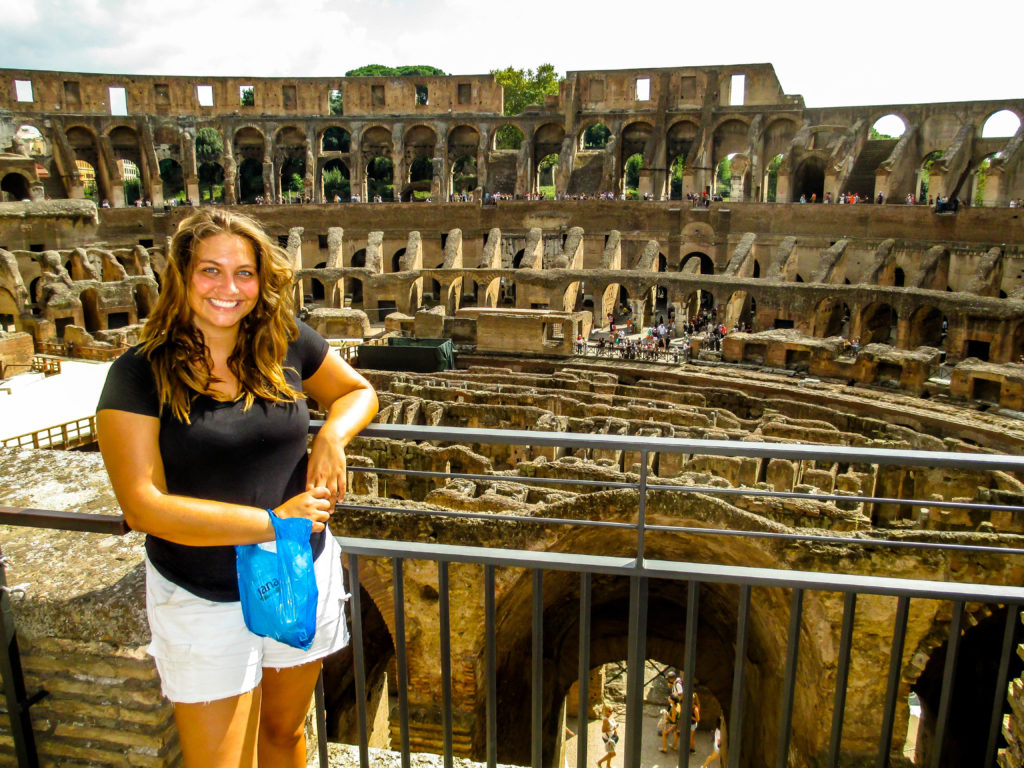 Overweight and traveling girl standing in front of the Coliseum