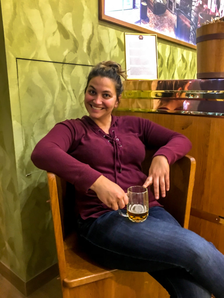 Girl sitting drinking a beer in a beer spa prague