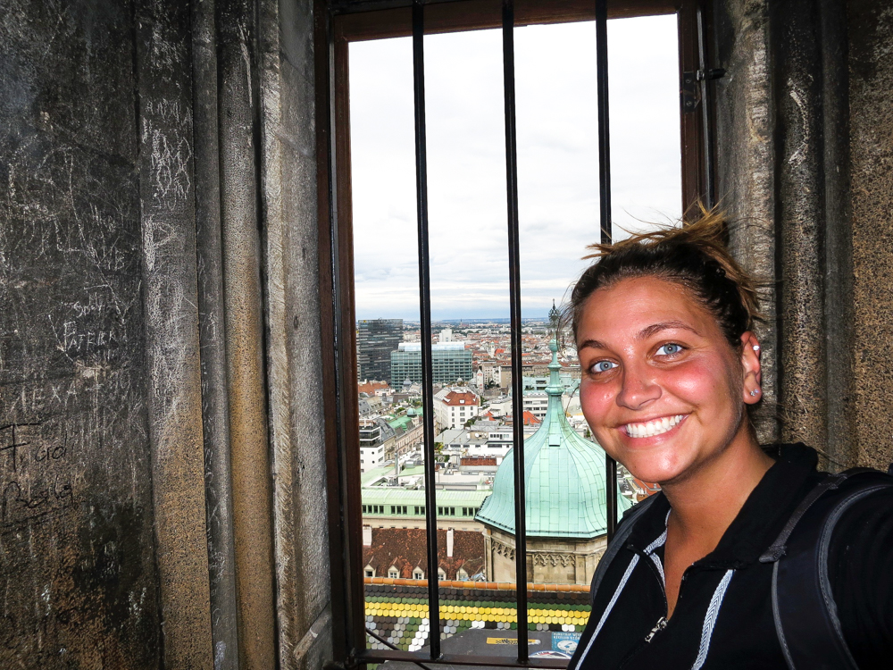 Girl at the top of St. Stephens Cathedral, standing by a window overlooking Vienna