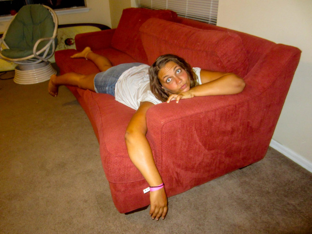Girl laying on a red couch