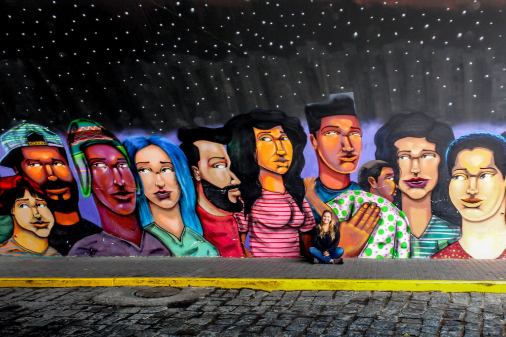 Girl in front of mural of different colored people