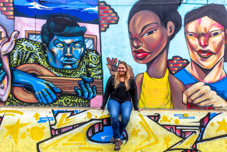 Girl sitting on a half wall in front of a mural.