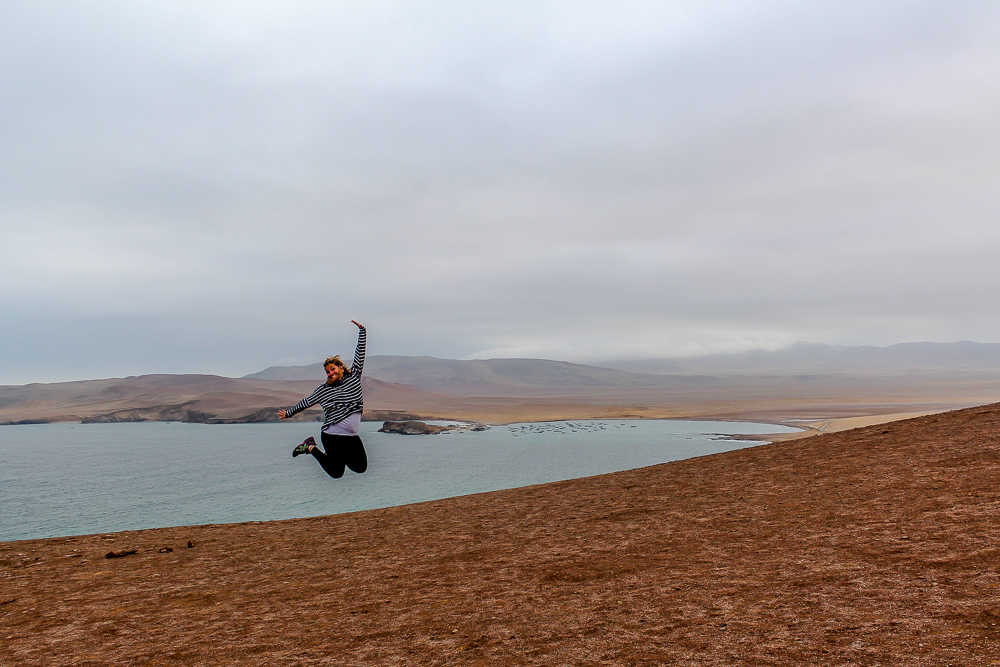 Girl jumping in a desert in Peru