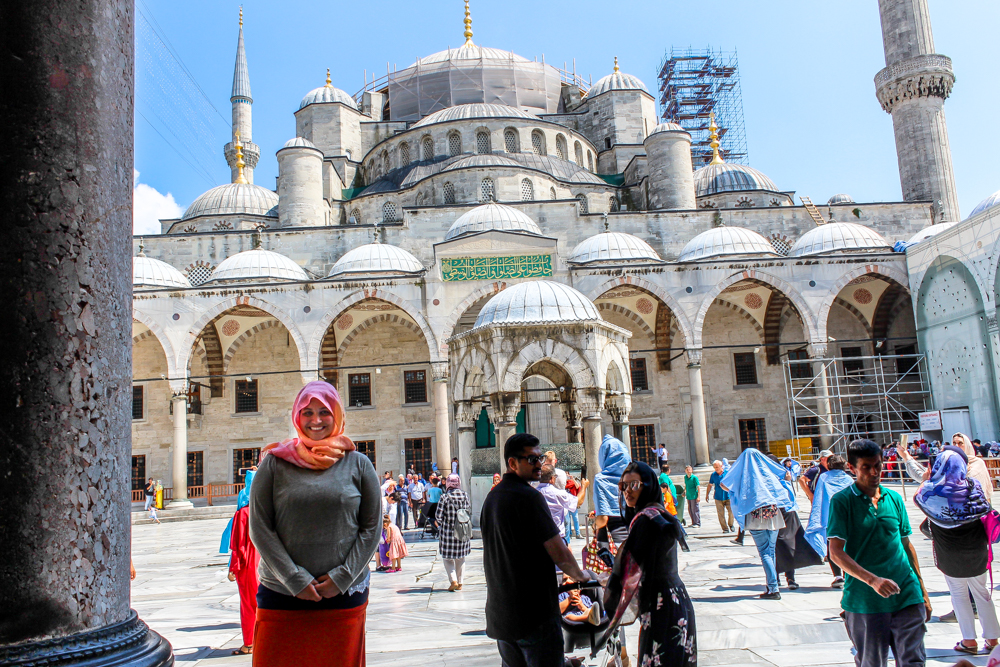 Overweight and traveling girl in front of a mosque in Istanbul