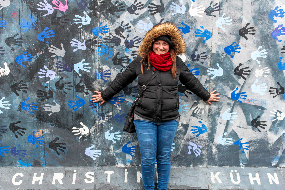 Overweight and traveling  girl in front of Berlin wall