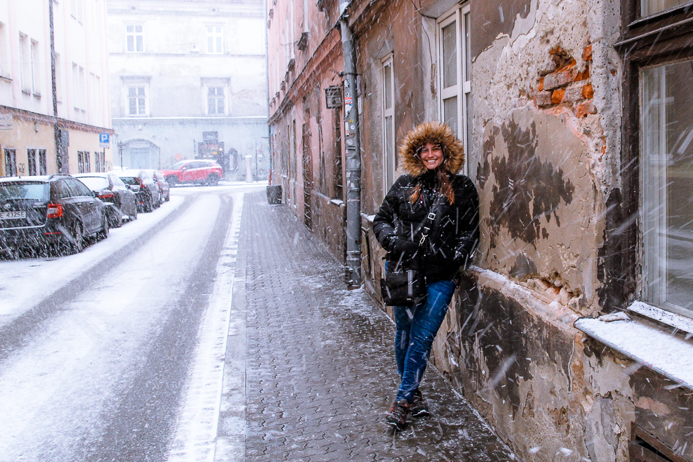 Girl leaning on wall in snowy Krakow Poland