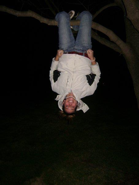 girl hanging upside down from tree branch